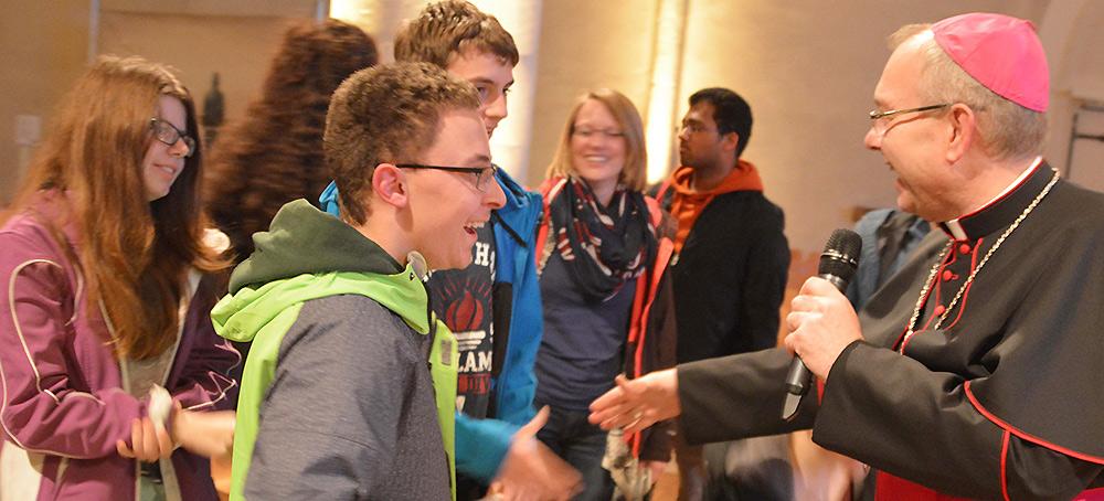 Weihbischof Hegge im Gespräch mit jungen Menschen.